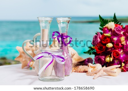 Decorative glass of champagne, wedding cake and bridal bouquet on a decoration table against a tropical caribbean beach, Dominican Republic. Fantastic dinner sweets near the sea on wedding day. - stock photo