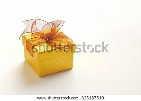 Decorative golden gift box with brown tie and grated texture. Elevated view. White isolated background.  - stock photo