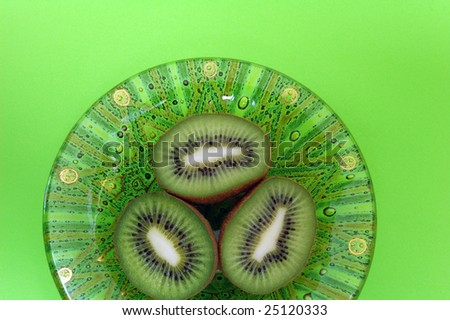 Decorative green bowl with halves kiwi on green background