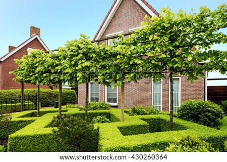 Decorative green buxus bushes and trees in front of a beautiful house in the Netherlands - stock photo