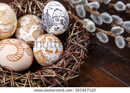 Decorative hand-painted Easter eggs in a nest on a wooden table. willow branches with blossoms. easter themed. Happy Easter - stock photo