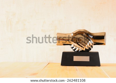 decorative handshake gadget over wooden table. business concept - stock photo