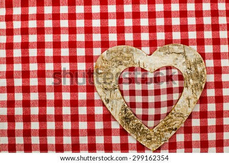 Decorative heart from eco-friendly organic natural birch bark on a white red checkered background - stock photo