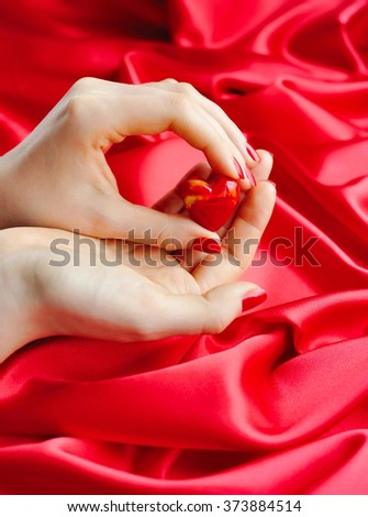 Decorative Heart in women's hands against a background of red silk