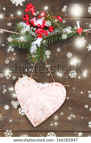 Decorative heart on rope, on wooden background
