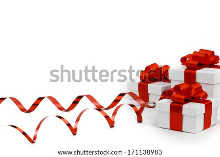Decorative holiday gifts in white boxes with red ribbons on white background