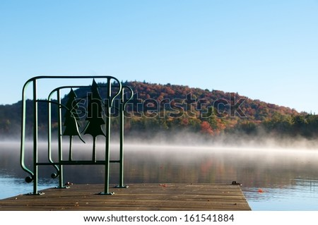 Decorative iron hand rail is attached to the dock with a view of the distant Adirondack mountain - stock photo