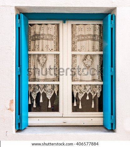 Decorative, lace window in France with turquoise shutters - stock photo