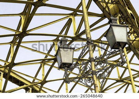 Decorative lamps hanging from old bridge - stock photo