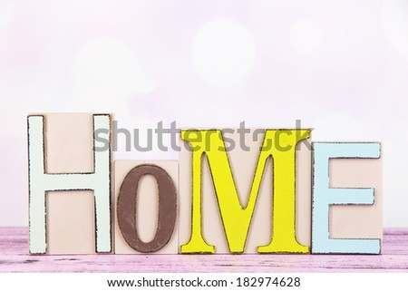 Decorative letters forming word HOME on table on bright background