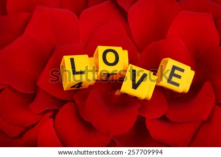 Decorative letters forming word LOVE on petals of roses background - stock photo