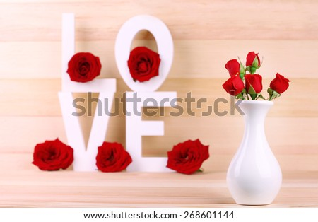 Decorative letters forming word LOVE with flowers on wooden background - stock photo