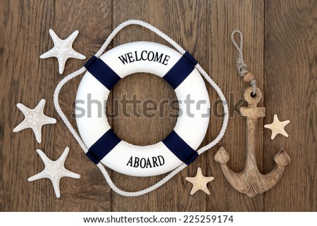 Decorative lifebuoy, anchor and starfish sea shells over old oak background. - stock photo