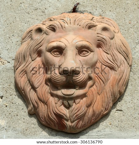 decorative lion head in terracotta hanging on wall, Tuscany, Italy - stock photo