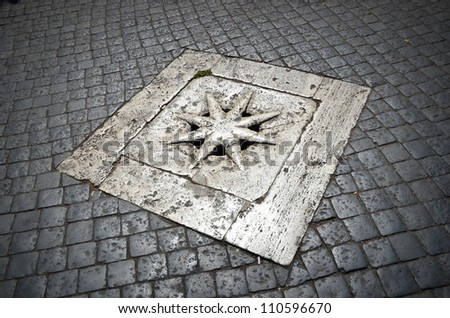 Decorative manhole cover on cobblestone road, Piazza di Spagna, Rome - stock photo