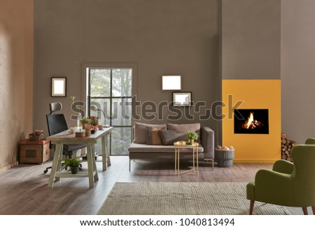 Decorative modern home office interior. Brown and yellow stone wall detail with fireplace.  Wooden working table and grey sofa with green armchair furniture. new style home office plan.