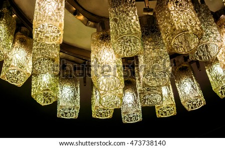 Decorative modern shaped lamps on ceiling, golden lamps with light against dark background, many modern ceiling lamps with golden ornament, high quality resolution