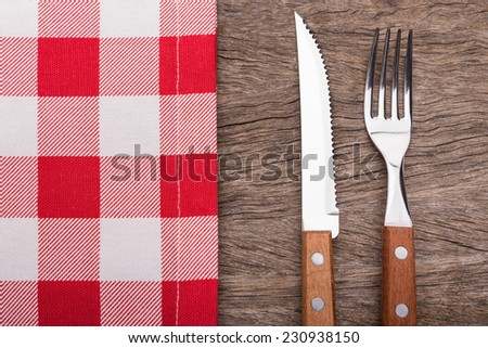 Decorative napkin, knife and fork. On wooden texture. - stock photo