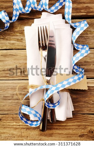 Decorative Oktoberfest table setting in a tavern or restaurant with a knife and fork tied with a tag on a napkin with a coiled party streamer in the blue and white Bavarian colors, overhead view - stock photo