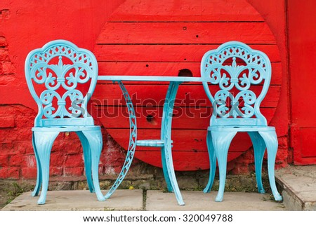Decorative old table and chairs in the street - stock photo