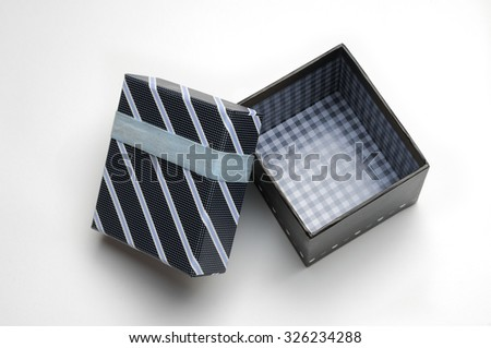 Decorative open black gift box with with ribbon and blue diagonal lines painted with dots. Top view. White isolated background.