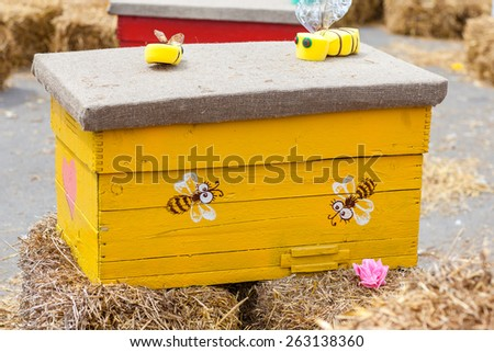 Decorative painted beehive with bees artificial decorative. Standing on a haystack. Original design ethno, country house for bees. - stock photo