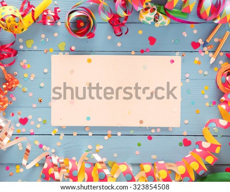 Decorative party frame of colorful spiral streamers and confetti over a rustic blue wood background with central blank card with copyspace for your greeting or invitation - stock photo