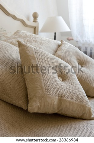 Decorative pillow on a bed in a bedroom - stock photo