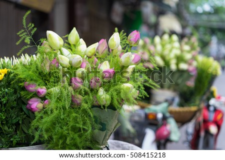 Decorative pink and green lotus flower bouquet on bike on Hanoi street, Vietnam