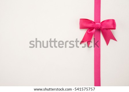 Decorative pink ribbon and bow on a white background