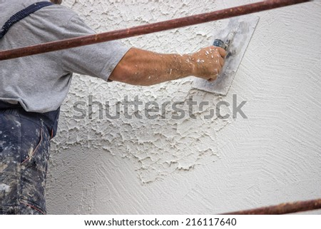 Decorative plaster applied on the surface by a steel trowel. White cement based decorative top coat plaster resistant on outside whether conditions. Selective focus. - stock photo