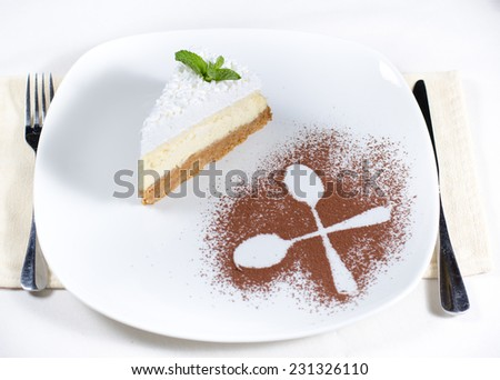 Decorative plating and presentation of a slice of creamy cheesecake viewed from above with the outline of two crossed spoons in sprinkled cocoa powder alongside - stock photo