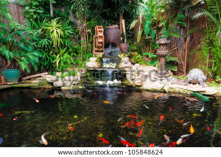 Decorative pond with fountain and gold fish - stock photo
