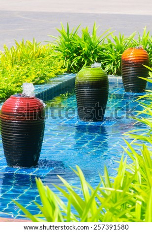 Decorative pond with fountain and green garden - stock photo