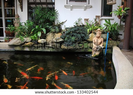 Decorative pond with gold fish in luxury garden home - stock photo