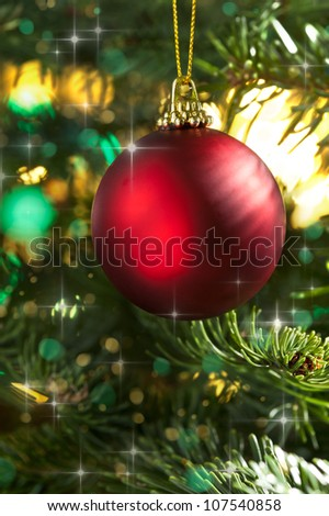 Decorative red bauble in a Christmas tree in front of a glitter background - stock photo