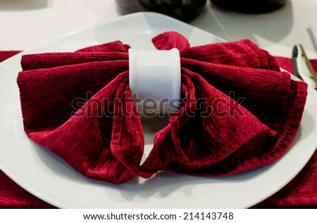 Decorative red linen serviette or napkin carefully folded and displayed on a white side plate on a formal dining table