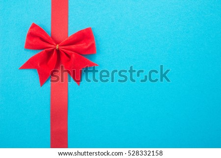 Decorative red ribbon and bow on a blue background