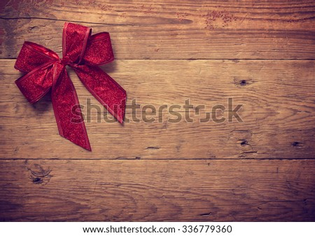 Decorative red ribbon and bow over wooden background - stock photo