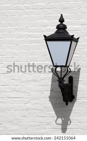 decorative retro lantern on white painted wall - stock photo