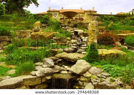 Decorative rocks near a small pond in a garden - stock photo