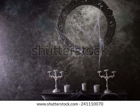 Decorative Round Frame Above Candles and Candelabras on Eerie Cobweb Covered Mantle in Haunted House Setting - stock photo