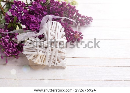Decorative rustic heart and  fresh white and violet lilac flowers in ray of light  on white painted wooden planks. Selective focus. Place for text. - stock photo