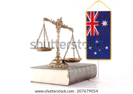 Decorative Scales of Justice on the book with Australian flag on white. Law and order concept - stock photo