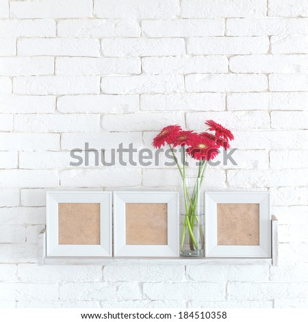 Decorative shelf on white brick wall with flowers in vase on it - stock photo