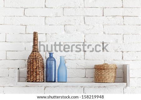 Decorative shelf on white brick wall with vintage bottles and wicker jars on it - stock photo