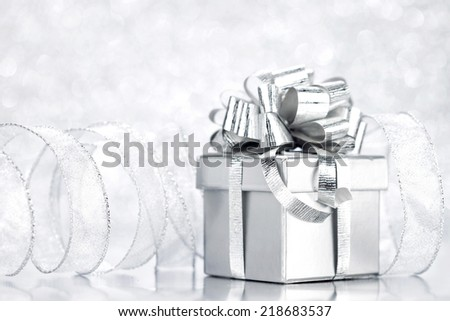 Decorative silver box with holiday gift on shiny glitter background