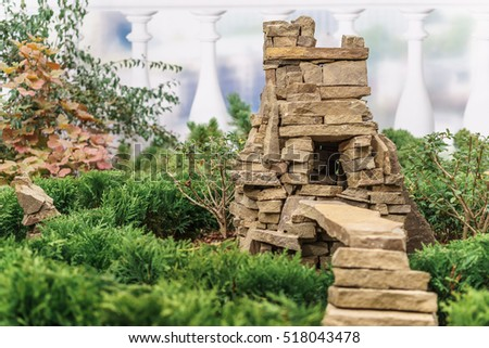 Decorative small house for garden in the form of a stone cave with a ladder