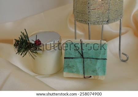 Decorative soap and lotion, on silk with candle base - stock photo