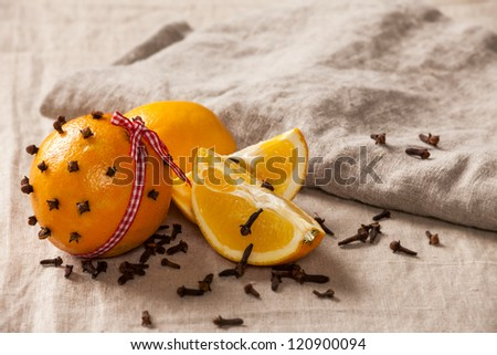 "Decorative, sparse christmas arrangement with greeting card copyspace for ""Merry Christmas""-text. Orange with clover and ribbon on a brown table cloth. Shallow focus. - stock photo"